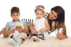 Mamma och barn med smartphones arkivbilder