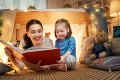 Mamma och barn som l?ser en bok fotografering för bildbyråer