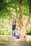 Mamma och barn som spelar i ett pappfartyg field treen Fotografering för Bildbyråer