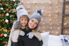 Mamma och dotter, grå hatt, julgran arkivbild