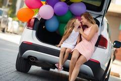 Mamma och dotter i en bil med ballonger Arkivbilder