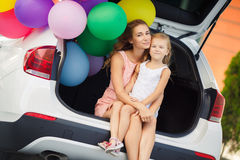 Mamma och dotter i en bil med ballonger Royaltyfri Bild
