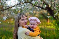 Mamma och dotter i en blommande trädgård Arkivbilder