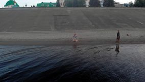 Mamma och dotter, k?rning, lek med en brun hund labrador p? stranden vid floden Flyg- filmande arkivfilmer