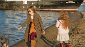 Mamma och dotter, k?rning, lek med en brun hund labrador p? stranden vid floden Flyg- filmande lager videofilmer