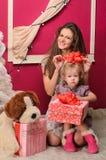 Mamma och dotter med gåvor inomhus arkivbilder