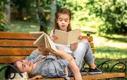 Mamma och dotter på en bänk som läser en bok Royaltyfri Foto