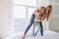 Mamma och dotter som har gyckel hemma royaltyfria bilder