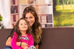 Mamma och dotter som poserar lyckligt inomhus att sitta in royaltyfria foton
