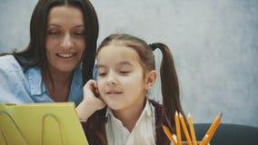 Mamma och dotter som sitter på tabellen på en grå bakgrund Under denna läsning böcker, leenden, kramar Begrepp av stock video