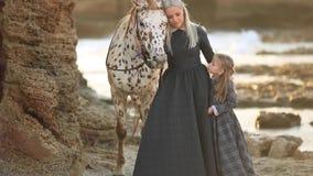 Mamma och dotter som slår en vit häst
