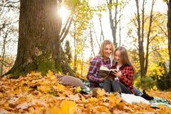 Mamma och dotter som tillsammans läser i parkera arkivbilder