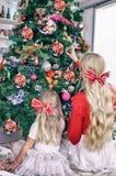 Mamma- och dotterblondin med pilbågar och att sitta på julgranen och att dekorera den arkivfoton