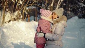 Mamma- och dotterkram i förorterna i vinter lager videofilmer
