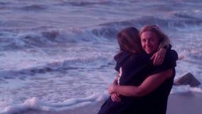 Mamma- och dotterkram, skratt, leende, mot bakgrunden av havet, stora vågor, skum, strand arkivfilmer