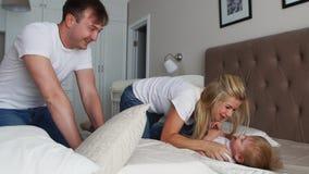 Mamma och fader som killar hennes barn folk-, familj-, gyckel- och morgonbegrepp - lyckligt barn med föräldrar som killar i säng  lager videofilmer