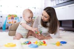 Mamma och hennes barn som spelar med den färgrika logiska leksaken Fotografering för Bildbyråer