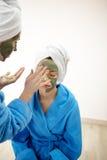 Mamma och hennes dotter som kyler i sovrummet och gör lera den ansikts- maskeringen Arkivbild