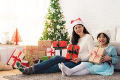 Mamma och hennes dotterflicka som utbyter gåvor Fotografering för Bildbyråer