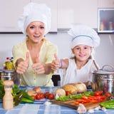 Mamma och liten dotter som inomhus lagar mat den vegeterian maträtten Royaltyfri Bild