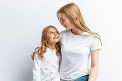 Mamma och liten dotter som ser de, den lyckliga familjen, isolerad bakgrund, gulligt och härligt Royaltyfri Foto
