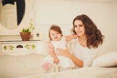Mamma- och liten flickasammanträde i rummet fotografering för bildbyråer