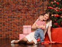 Mamma och liten son på julträdet arkivfoton