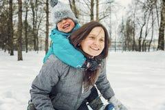 Mamma och liten son som spelar i den insnöade vintern arkivfoto