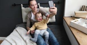 Mamma och litet barn som tar selfie i mysig vardagsrum stock video
