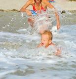 Mamma och son på stranden arkivbilder