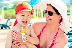 Mamma och son på stranden som skyddar huden från sollotion Royaltyfri Foto