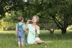 Mamma och son och såpbubblor i parkera royaltyfri fotografi