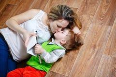 Mamma och son som spelar med minnestavlaPC, medan ligga på golvet Royaltyfri Fotografi