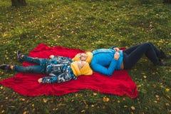Mamma- och sonlögn på en filt på gräset royaltyfri fotografi