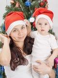 Mamma och unge på julgranen royaltyfri fotografi