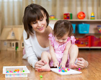 Mamma- och ungeflickan spelar leksaker i barnrum arkivfoton