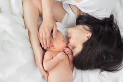 Mamma på en vit säng med ett nyfött Arkivbild