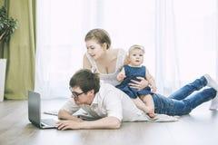 Mamma, papà e figlia della famiglia con un computer portatile insieme a casa felice Fotografie Stock