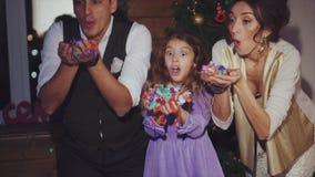 Mamma, papà felice e figlia soffianti celebrazione variopinta dei coriandoli del Natale