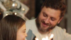 Mamma, Papa en Dochterzitting naast een verfraaide Kerstboom met sterretjes in langzame motie stock videobeelden