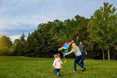 Mamma, papa en kind die een vlieger vliegen Het gelukkige familie spelen, het glimlachen stock foto's