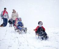 Mamma, papa met jonge geitjes die pret in de sneeuw hebben Stock Foto's
