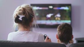 Mamma posteriore di vista con il figlio che gioca il video gioco del tiratore archivi video