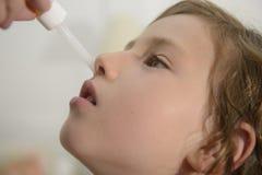 Mamma som applicerar näsdroppar Arkivfoto