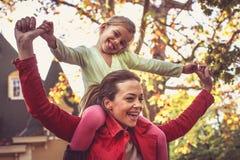 Mamma som bär mig på skuldror Gör mig lycklig Arkivbild