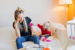 Mamma som frustreras av hennes litet barn arkivbild