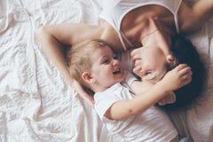 Mamma som kopplar av med hennes lilla son fotografering för bildbyråer