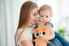 Mamma som kramar och kysser hans lilla dotter arkivfoton