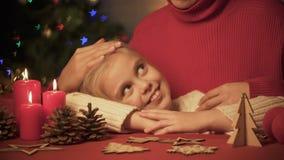 Mamma som kramar och slår den lilla gulliga flickan, dekor X-mas på tabellen, moussera för träd lager videofilmer