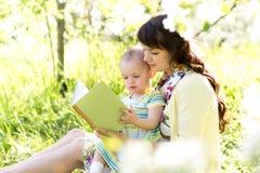 Mamma som läser en bok för att lura utomhus Royaltyfri Fotografi